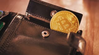 Three bitcoin coins in the leather wallet