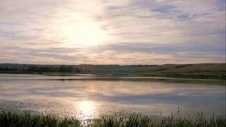Time lapse of clouds dancing in the wind above a beautiful pond. Sunset footage with moving clouds reflection in a pond.