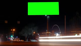 Timelapse highway night city. Greenkey billboard for advertisement at twilight time with light trails on the road at dusk, business advertising concept.