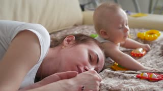 Tired young mother, fell asleep while her baby doesn't sleep