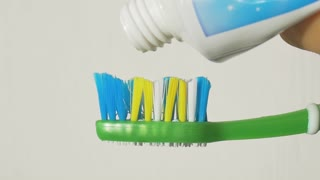 Toothpaste in a tube on a toothbrush close-up.