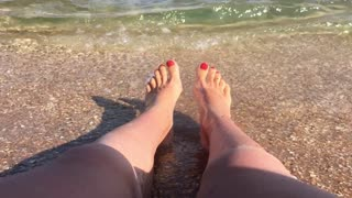 Tourist Sitting on the Beach and Getting her Feet Wet because of a Wave.