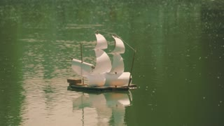 Toy sail ship floats on the water.
