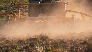 Tractor preparing land with seedbed cultivator as part of pre seeding activities of agricultural works at farmlands. Farmer in tractor preparing land with seedbed cultivator at sunset.