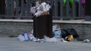 Trash spilling out of overfilled trash plastic bag on city street.
