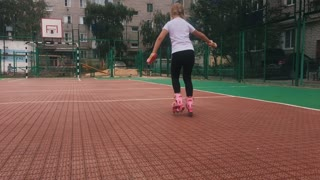 Trendy girl roller-skating on sports ground.