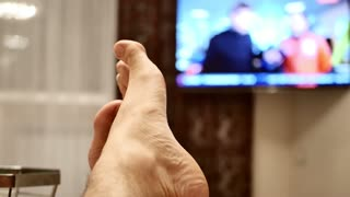 TV, television watching news with feet on the table and remote in hand.