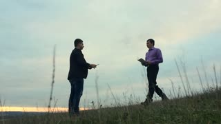Two businessman farmers shake hands with each other firmly. They talk on the field against a beautiful sunset, they use a tablet and papers.