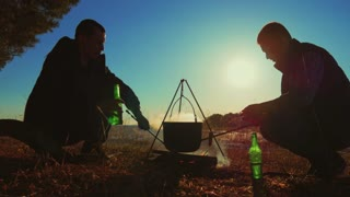 Two fellow campers making tea and preparing food in the forest