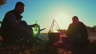 Two fellow campers preparing food in the forest. Two cheerful friends by the bonfire at sunset. Аdventure, travel, tourism and people concept.