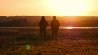 Two friends sunset to go forward, the concept of adventure travel, a backpack on the shoulders