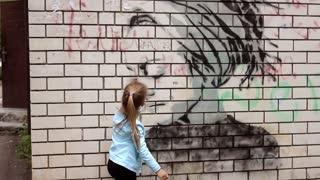 Urypinsk - May 31, 2017: Graffiti on a urban wall near Lenina street . Close-up of a girl. Girl draws with chalk on brick wall.