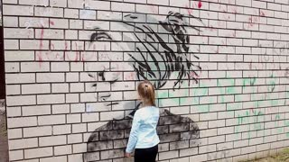 Urypinsk - May 31, 2017: Graffiti on a urban wall near Lenina street . Close-up of a girl. Girl draws with chalk on brick wall.