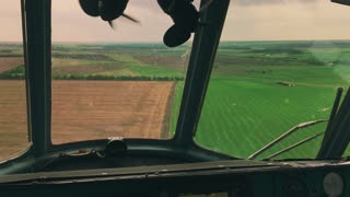 View from inside of helicopter cockpit of meadows and fields. View from helicopter cabin during flight.