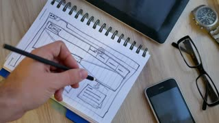 Web designer draws the layout of the site in his book.