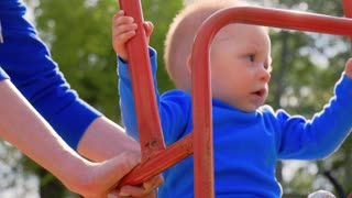Woman and her little son playing a swing on the playground at the park.