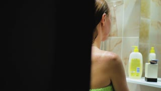 Woman caresses her skin in bathroom