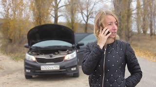 Woman having car troubles on the road, calling on the cell phone for emergency repair service. A woman calls for assistance after her car broke down.