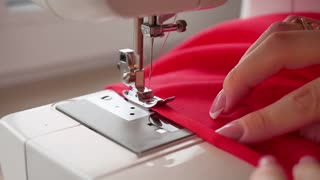 Woman sews on the modern sewing machine. Sewing machine sews close up the action in slow motion.
