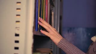 Woman taking book from library bookshelf. Young librarian searching books and taking one book from library bookshelf