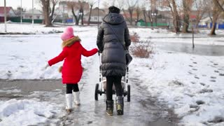 Woman with an adult daughter and a stroller on a walk in winter park