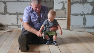 Working fun grandfather and grandson on the construction site. Grandfather teaches his grandson the baby to hammer nails. Family concept.