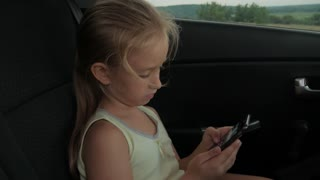 Young attractive blonde girl sitting in the car and use smartphone.