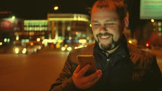 Young bearded trendy man standing with smartphone in the street city at night time.