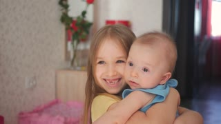 Young beautiful girl holding her little brother in her arms smiling happily and looking at camera