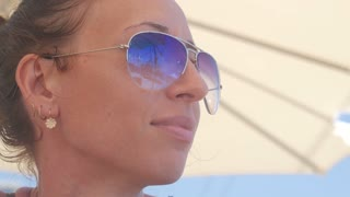 Young beautiful girl in sunglasses beach reflection. concept of holiday at sea.