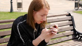 Young beautiful woman dial a text on the mobile phone in park. Side view of a college girl text messaging mobile phone in the park.