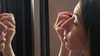 Young beautiful woman doing makeup in front of a mirror.