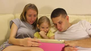 Young Caucasian Family of Three Watching Funny Video on Cellphone Together