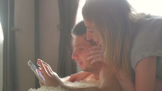 Young couple laughing watching movies in bed on digital tablet computer