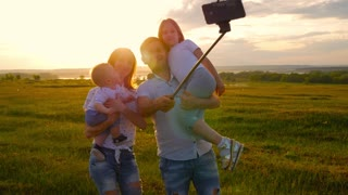 Young family doing selfie at sunset. They have fun and spend time together. The concept of a friendly and cheerful family.