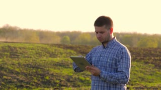 Young farmer holding tablet in front of tractor in field. Farmer controls the work in the field over it's tablet. Seasonal agricultural workers.