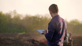 Young farmer holding tablet in front of tractor in field. Seasonal agricultural worker. Concept ecology, transport, farmers, clean air, food, bio product.