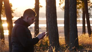 Young fit man listening music in headphones before run, training. Men during run through woods. Sportsman wears headphones in the woods.