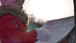 Young girl blowing snow in frosty winter Park. Outdoors. Flying Snowflakes. Sunny day.