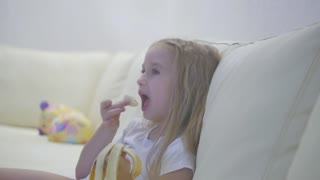 Young girl eating banana sitting at home.
