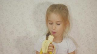 Young girl eating banana sitting at home.