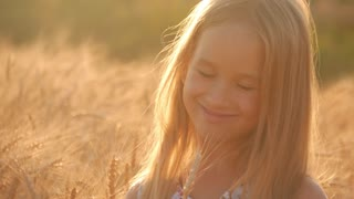 Young girl in a golden field during sunset.