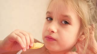Young girl indoors eating chips smiling. Eating harmful food.