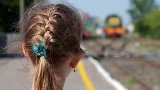 Young girl looks at a departing train.