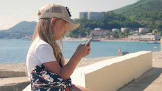Young girl using a Mobile Phone Sitting on Embankment near the Sea in the Summer. Child controls Smartphone with finger gestures and looks at the social networks.