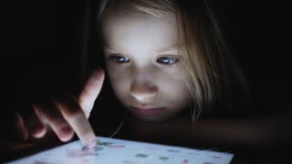 Young girl using tablet computer becuause of internet addiction and insomnia lying on bed at home at late night. Closeup of a young girl's pointing finger to a tablet monitor.