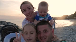 Young, happy family recording video, taking selfie near sea at sunset.