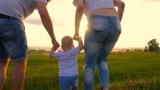 Young happy family with baby. They go to the picturesque green field at sunset. The boy is raised by the parents. Sunset over the background. 4K UHD video 3840X2160