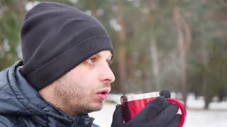 Young man drinking tea or coffee in forest. Traveler man in forest in winter time. Man traveler hands holding cup of tea.