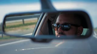 Young man in sunglasses is driving a car. Reflection face in rearview mirror of vehicle.